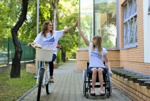 girl on the bike and girl in the wheelchair give each other a high five